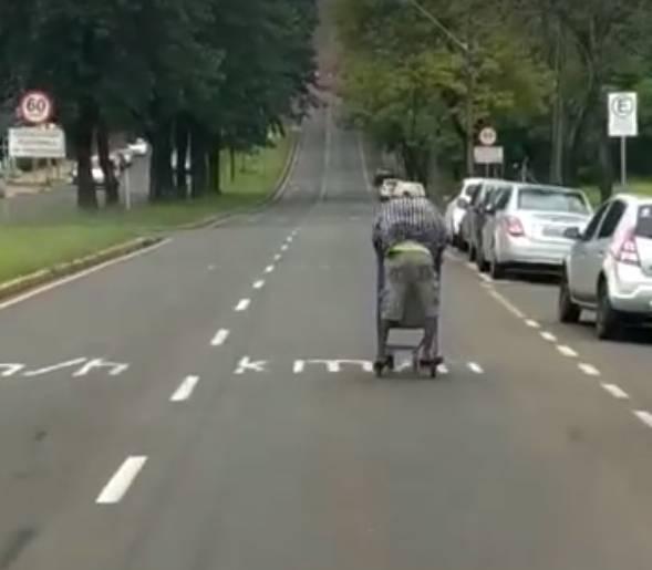 Homem desce avenida pilotando um carrinho de supermercado